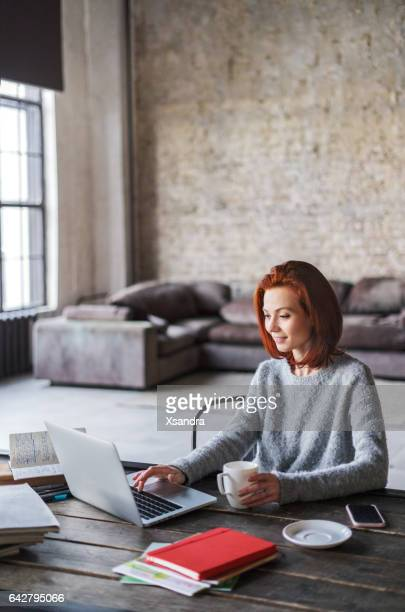 young woman working in a loft apartment with a laptop computer - dyed red hair stock pictures, royalty-free photos & images
