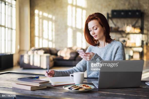 Jonge vrouw die werkt in een loft-appartement met een laptopcomputer