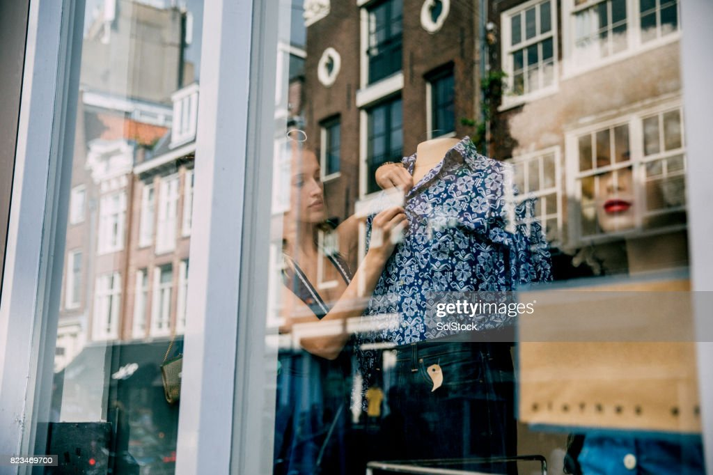 Young Woman Working in a Shop Window : Stock Photo