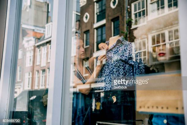 young woman working in a shop window - high street stock pictures, royalty-free photos & images