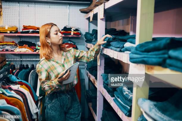 ヴィンテージ衣料品店で働く若い女性 - 服装 ストックフォトと画像