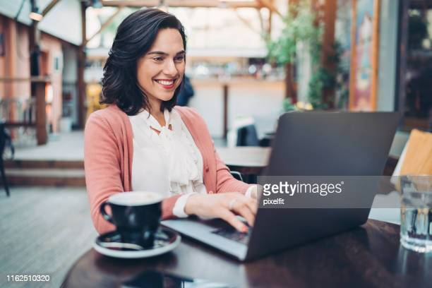 young woman working in cafe - public building stock pictures, royalty-free photos & images