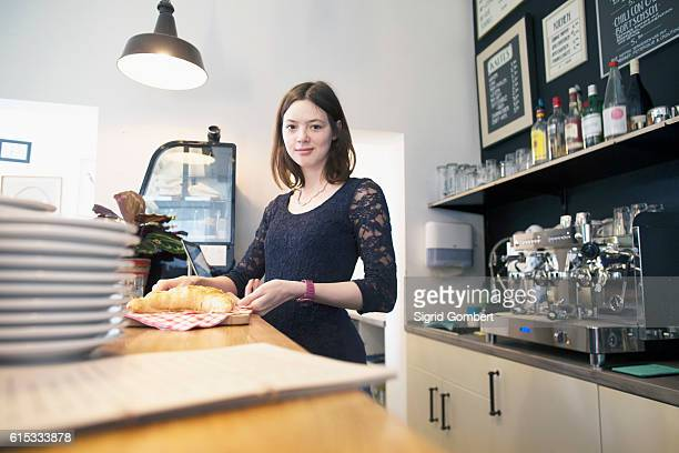 young woman working in coffee shop serving croissant, freiburg im breisgau, baden-württemberg, germany - sigrid gombert stock-fotos und bilder