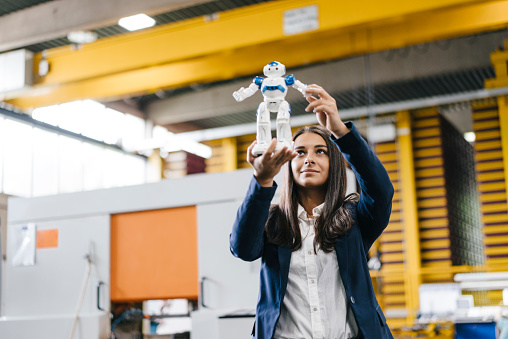 Young woman working in distribution warehouse, looking at toy robot - gettyimageskorea