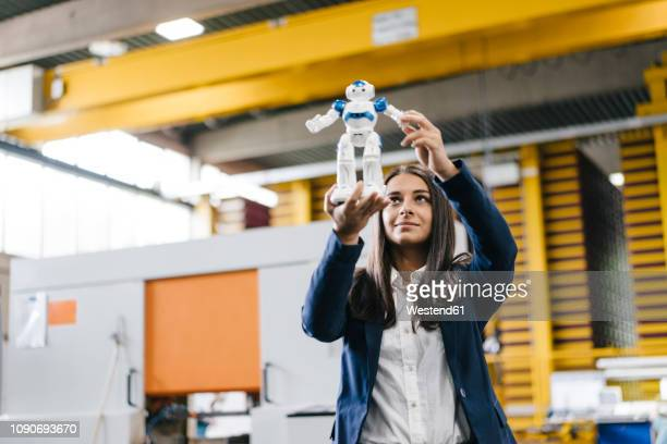 young woman working in distribution warehouse, looking at toy robot - intelligenz stock-fotos und bilder