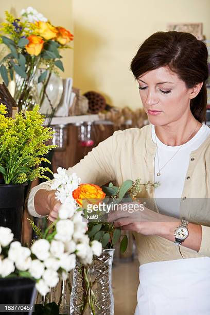 young woman working in florist shop arranging flowers - kali rose stock pictures, royalty-free photos & images