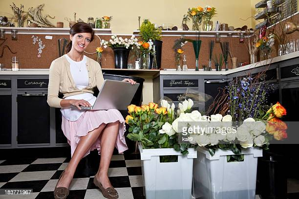young woman working in florist shop with laptop - kali rose stock pictures, royalty-free photos & images
