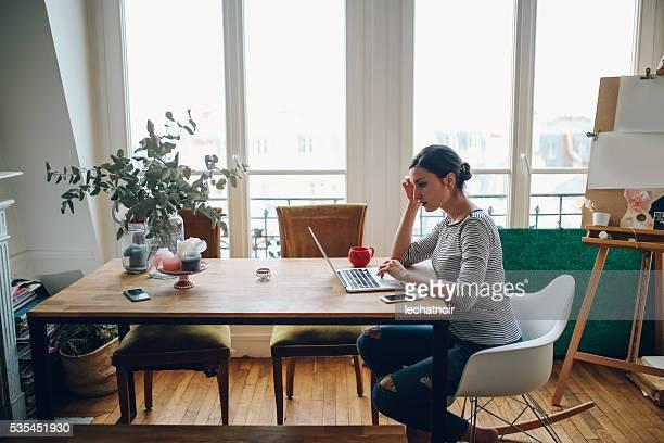 Jeune femme travaillant dans son appartement parisien espace de travail