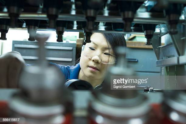 young woman working in industrial workshop - sigrid gombert foto e immagini stock