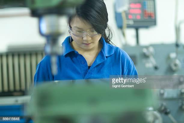 young woman working in industrial workshop - sigrid gombert 個照片及圖片檔