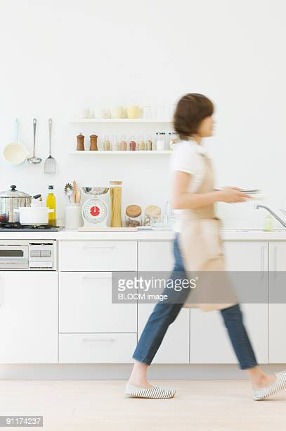 Young woman working in kitchen, blurred motion