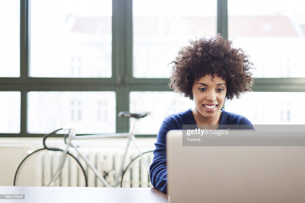Young Woman Working in Loft Space Behind Laptop : Stock Photo