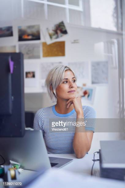 young woman working in office, sitting at desk, smiling - hand on chin stock pictures, royalty-free photos & images