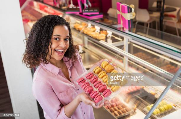 Young woman working in pastry shop with french macarons