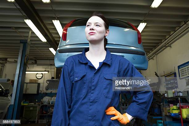 Young woman working in repair garage, standing in front of hoist