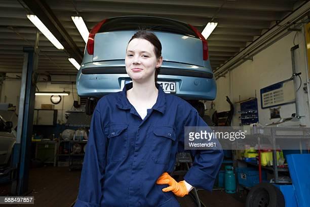 Young woman working in repair garage, standing in front of hoist