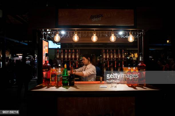 A young woman working in the Aperol booth inside the market of San Miguel in Madrid Spain on 29 April 2018 On weekends the city of Madrid offers a...