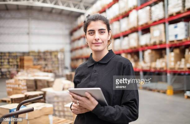 junge frau, die im lager arbeiten - lagerhaltung stock-fotos und bilder