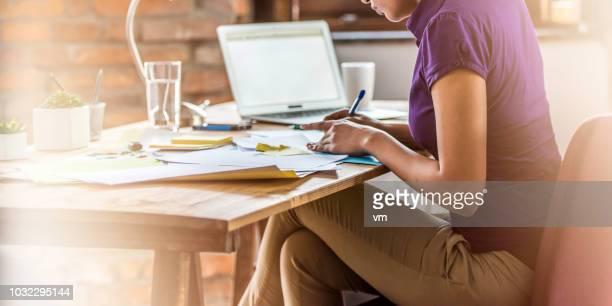 仕事の若い女性 - 足を組む ストックフォトと画像