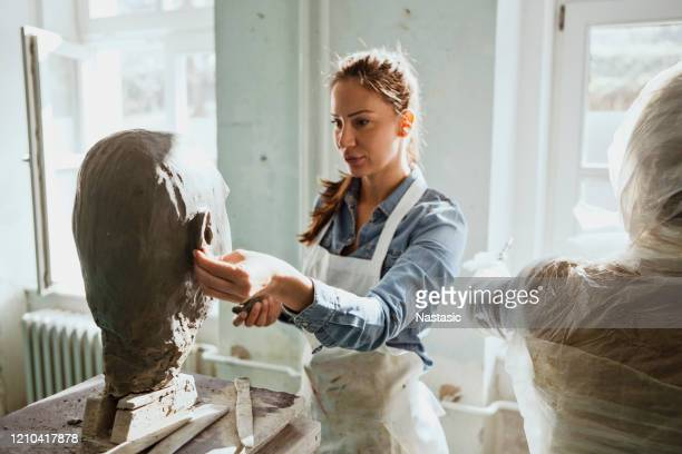 young woman working on a head sculpture out of clay in a studio workshop - sculpture stock pictures, royalty-free photos & images