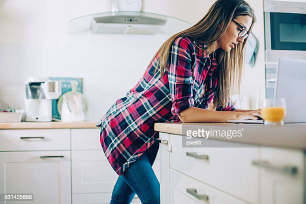 Young woman working on a laptop from her kitchen
