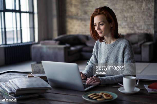 Young woman working on a laptop in a loft apartment