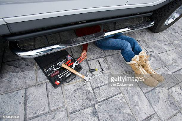 Young Woman Working on Car