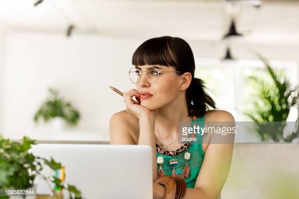 junge frau arbeitet am computer im umweltfreundlichen büro - schriftsteller stock-fotos und bilder