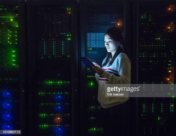 young woman working on digital tablet in server room - data center stock pictures, royalty-free photos & images