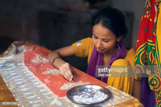 Young woman working on embroidery with pearls on a traditional Banarasi sari in the old city Varanasi Uttar Pradesh India
