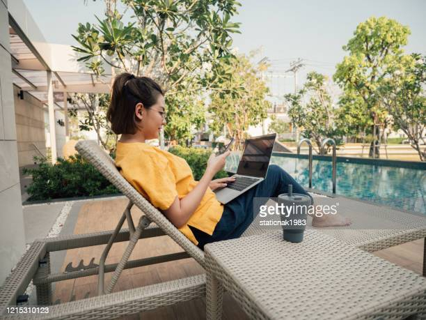 young woman working on her computer on vacation near pool. - nomadic people stock pictures, royalty-free photos & images