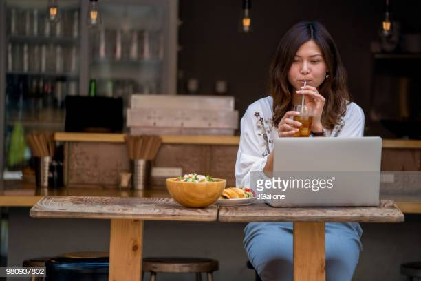 Young woman working on her laptop in a cafe