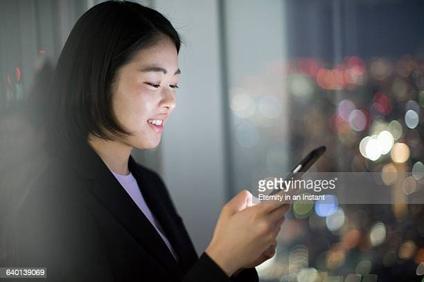 Young woman working on her phone by a window