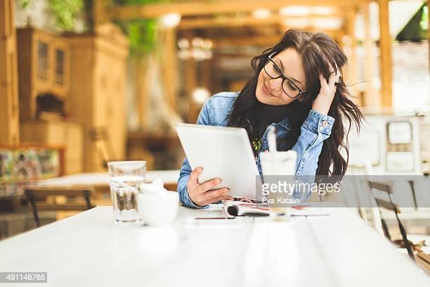 Jeune femme travaillant sur sa tablette dans le coffee shop