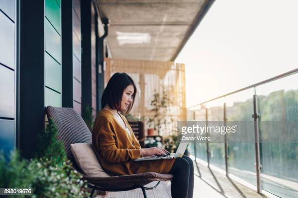 Young woman working on laptop in balcony