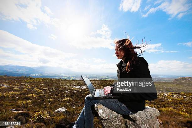 Young woman working on laptop in barren, windy wasteland