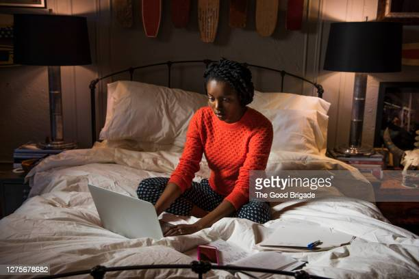 young woman working on laptop in bedroom - bed stock pictures, royalty-free photos & images