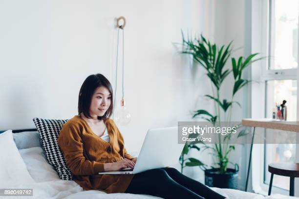 young woman working on laptop in bedroom - 若い女性だけ ストックフォトと画像
