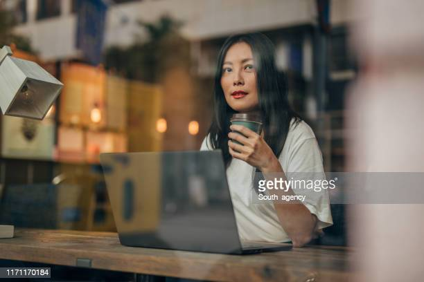 young woman working on laptop in cafe - fashionable stock pictures, royalty-free photos & images