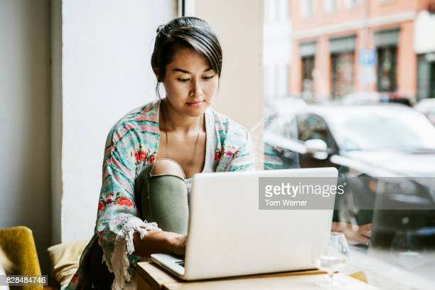 young woman working on laptop in cafe window - person on laptop stock pictures, royalty-free photos & images