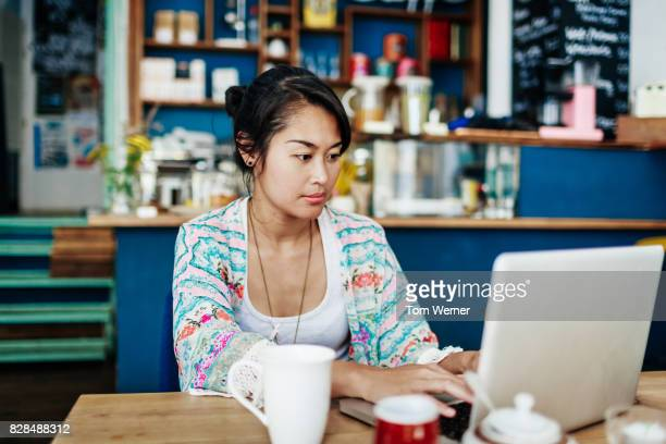Young Woman Working On Laptop In Colourful Coffee Shop
