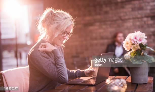 jonge vrouw die werkt op laptop outdoor. - witte boorden werker stockfoto's en -beelden