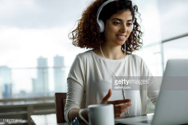 young woman working on laptop - showing stock pictures, royalty-free photos & images