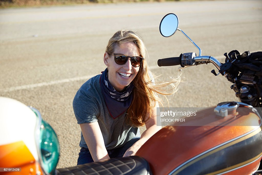 Young woman working on motorcycle : Stock Photo