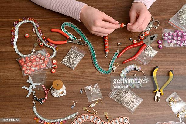 Young woman working on self-made jewelry