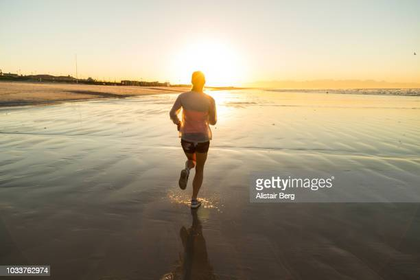 young woman working out on a beach at dawn - morning stock pictures, royalty-free photos & images