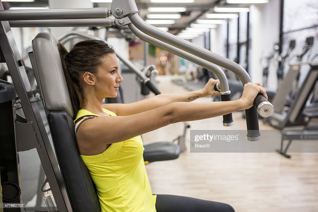Young woman working out on exercise machine in a gym. : Stock Photo
