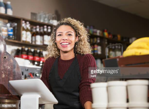 Young woman working the cash register at coffee shop