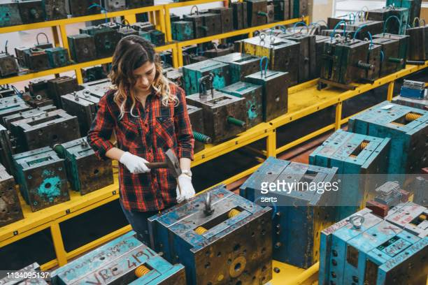 Young woman working with hammer in industrial building