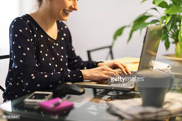 Young woman working with laptop at home, partial view